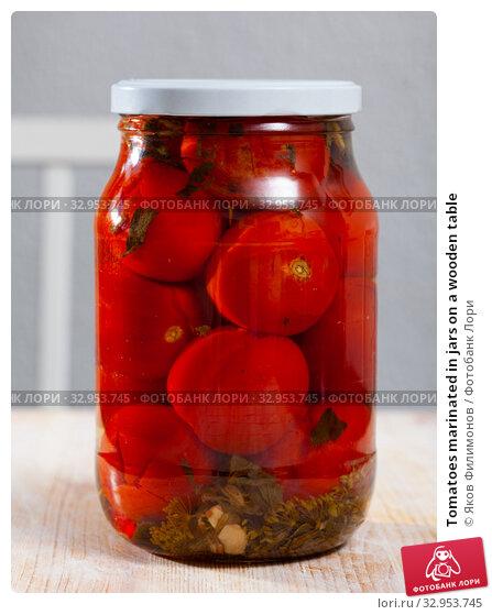 Tomatoes marinated in jars on a wooden table. Стоковое фото, фотограф Яков Филимонов / Фотобанк Лори
