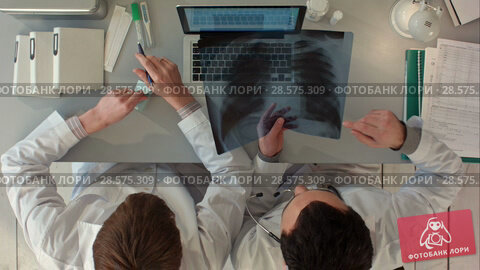 Купить «Top view of Doctors discussing intestines xray at medical office», видеоролик № 28575309, снято 28 ноября 2015 г. (c) Vasily Alexandrovich Gronskiy / Фотобанк Лори