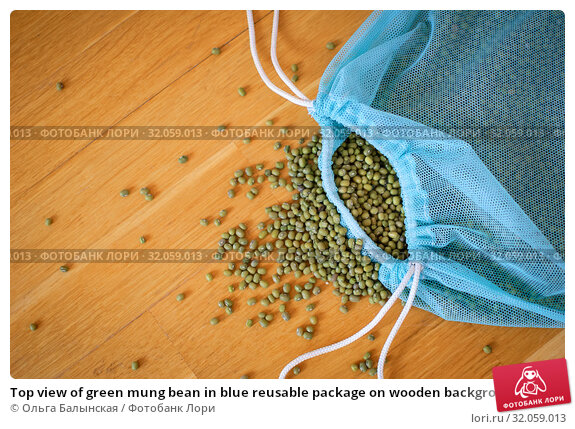 Top view of green mung bean in blue reusable package on wooden background. Healthy eating concept. Стоковое фото, фотограф Ольга Балынская / Фотобанк Лори