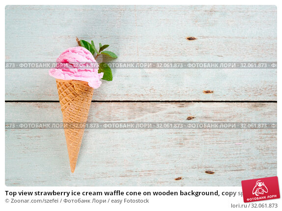 Top view strawberry ice cream waffle cone on wooden background, copy space on side. Стоковое фото, фотограф Zoonar.com/szefei / easy Fotostock / Фотобанк Лори