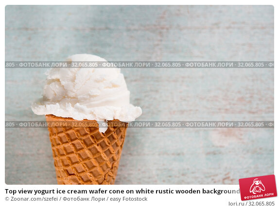 Top view yogurt ice cream wafer cone on white rustic wooden background. Copy space on side. Стоковое фото, фотограф Zoonar.com/szefei / easy Fotostock / Фотобанк Лори