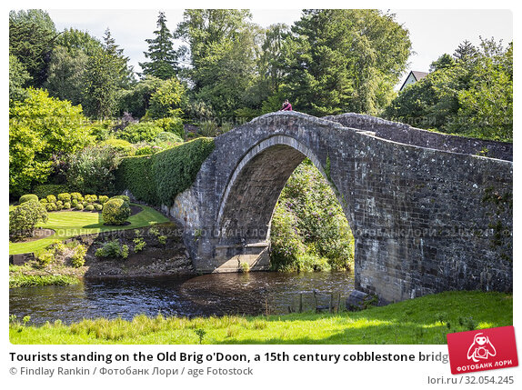 Tourists standing on the Old Brig o'Doon, a 15th century cobblestone bridge crossing the River Doon at Alloway, Ayrshire and was mentioned in the poem Tam O'Santer by Robert Burns. Стоковое фото, фотограф Findlay Rankin / age Fotostock / Фотобанк Лори