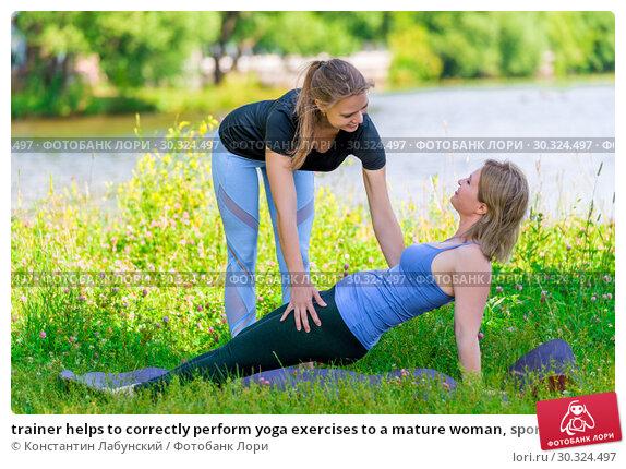 Купить «trainer helps to correctly perform yoga exercises to a mature woman, sports in the park in summer», фото № 30324497, снято 12 июля 2018 г. (c) Константин Лабунский / Фотобанк Лори
