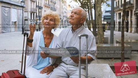 Купить «Traveling mature spouses resting on stone bench on city street, looking map», видеоролик № 27194057, снято 11 сентября 2017 г. (c) Яков Филимонов / Фотобанк Лори