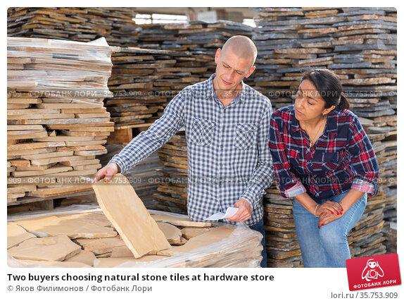Two buyers choosing natural stone tiles at hardware store. Стоковое фото, фотограф Яков Филимонов / Фотобанк Лори