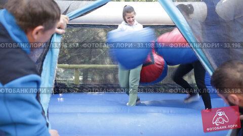 Two cheerful women having funny battle by big boxing gloves on inflatable arena at amusement park. Стоковое видео, видеограф Яков Филимонов / Фотобанк Лори