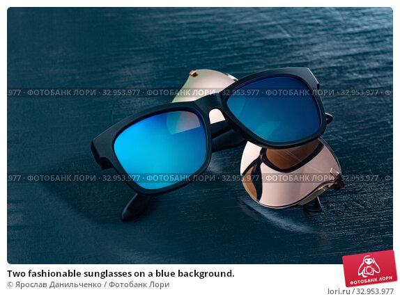 Two fashionable sunglasses on a blue background. Стоковое фото, фотограф Ярослав Данильченко / Фотобанк Лори