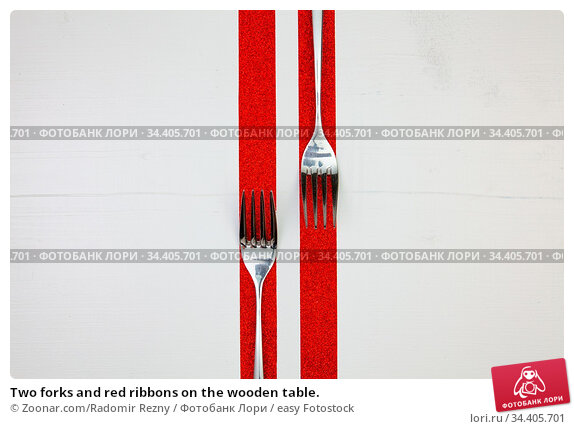 Two forks and red ribbons on the wooden table. Стоковое фото, фотограф Zoonar.com/Radomir Rezny / easy Fotostock / Фотобанк Лори
