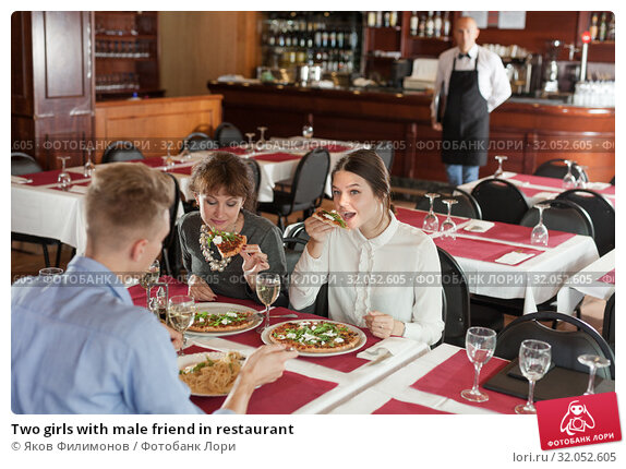 Two girls with male friend in restaurant. Стоковое фото, фотограф Яков Филимонов / Фотобанк Лори