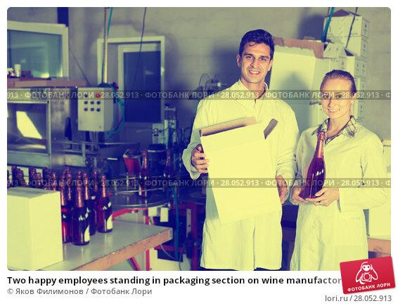Купить «Two happy employees standing in packaging section on wine manufactory», фото № 28052913, снято 21 сентября 2016 г. (c) Яков Филимонов / Фотобанк Лори