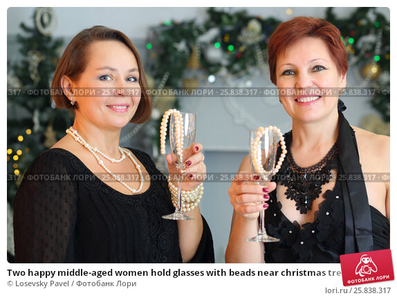 Купить «Two happy middle-aged women hold glasses with beads near christmas tree», фото № 25838317, снято 24 декабря 2014 г. (c) Losevsky Pavel / Фотобанк Лори