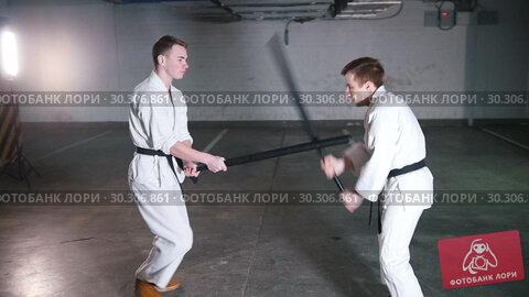 Купить «Two men in kimono training kendo on a parking lot», видеоролик № 30306861, снято 20 марта 2019 г. (c) Константин Шишкин / Фотобанк Лори
