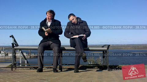 Купить «two men sitting outdoors on a bench with a book», видеоролик № 28574885, снято 12 октября 2015 г. (c) Vasily Alexandrovich Gronskiy / Фотобанк Лори