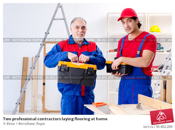 Two professional contractors laying flooring at home. Стоковое фото, фотограф Elnur / Фотобанк Лори