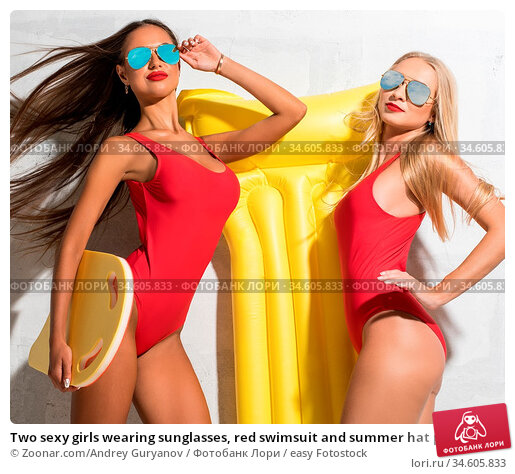 Two sexy girls wearing sunglasses, red swimsuit and summer hat posing... Стоковое фото, фотограф Zoonar.com/Andrey Guryanov / easy Fotostock / Фотобанк Лори