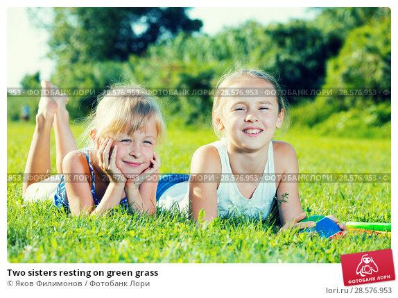 Купить «Two sisters resting on green grass», фото № 28576953, снято 20 июля 2017 г. (c) Яков Филимонов / Фотобанк Лори