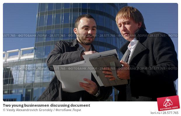 Купить «Two young businessmen discussing document», фото № 28577765, снято 25 июня 2018 г. (c) Vasily Alexandrovich Gronskiy / Фотобанк Лори