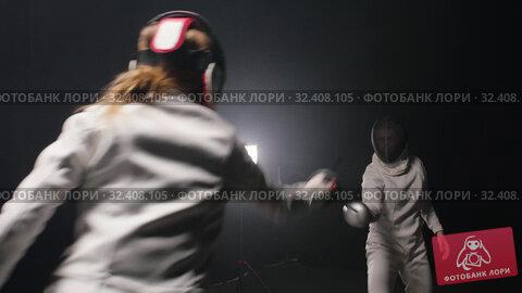 Купить «Two young women having training in a fencing duel in the smoky studio - greeting each other and starting the duel», видеоролик № 32408105, снято 3 апреля 2020 г. (c) Константин Шишкин / Фотобанк Лори