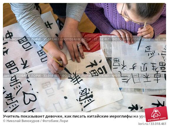 Учитель показывает девочке, как писать китайские иероглифы на уроке калиграфии в городе Москве, Россия (2020 год). Редакционное фото, фотограф Николай Винокуров / Фотобанк Лори
