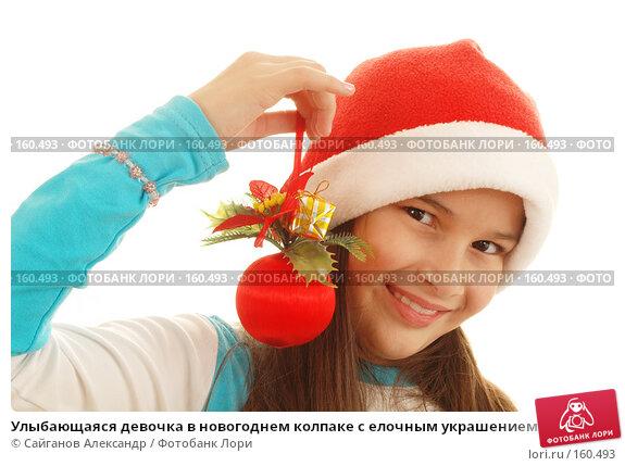 Улыбающаяся девочка в новогоднем колпаке с елочным украшением в руках, эксклюзивное фото № 160493, снято 19 ноября 2006 г. (c) Сайганов Александр / Фотобанк Лори