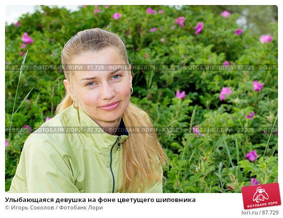 Улыбающаяся девушка на фоне цветущего шиповника, фото № 87729, снято 26 октября 2016 г. (c) Игорь Соколов / Фотобанк Лори