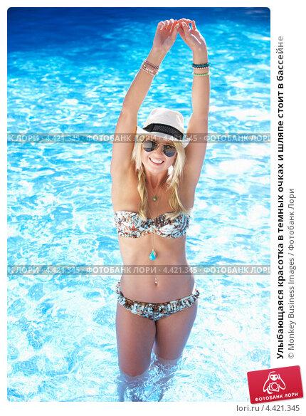 Улыбающаяся красотка в темных очках и шляпе стоит в бассейне, фото № 4421345, снято 10 июля 2012 г. (c) Monkey Business Images / Фотобанк Лори