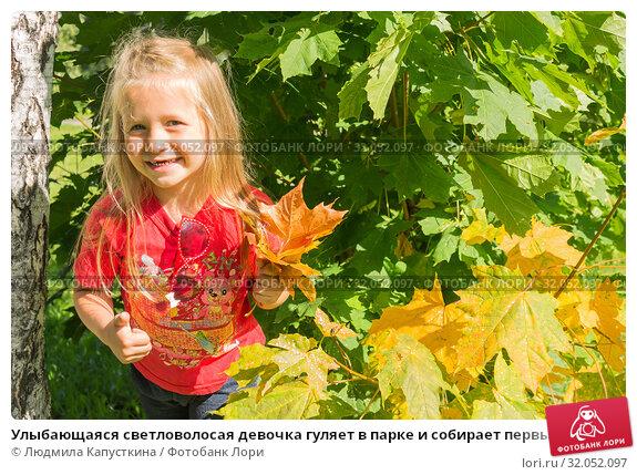 Улыбающаяся светловолосая девочка гуляет в парке и собирает первые пожелтевшие листья клёна (2019 год). Редакционное фото, фотограф Людмила Капусткина / Фотобанк Лори