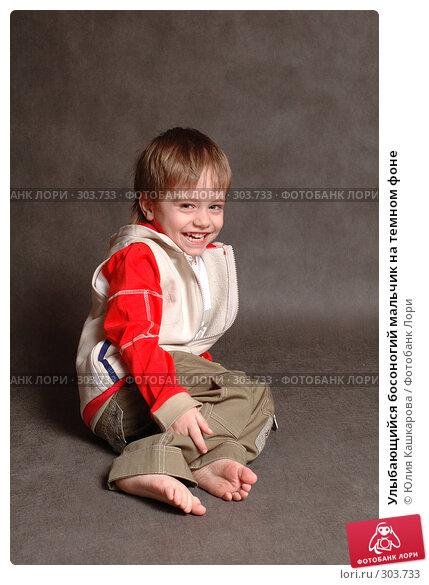 Улыбающийся босоногий мальчик на темном фоне, фото № 303733, снято 23 марта 2008 г. (c) Юлия Кашкарова / Фотобанк Лори
