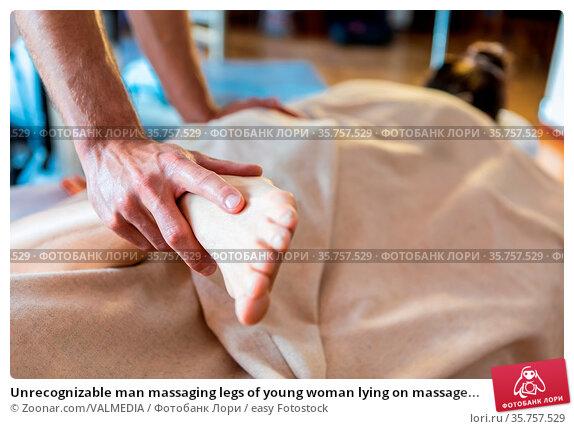 Unrecognizable man massaging legs of young woman lying on massage... Стоковое фото, фотограф Zoonar.com/VALMEDIA / easy Fotostock / Фотобанк Лори