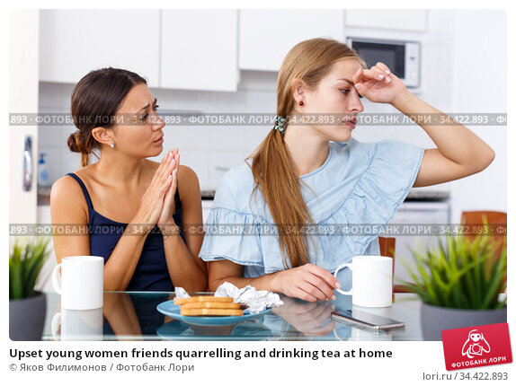 Upset young women friends quarrelling and drinking tea at home. Стоковое фото, фотограф Яков Филимонов / Фотобанк Лори
