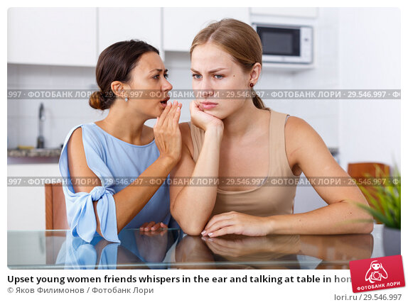 Купить «Upset young women friends whispers in the ear and talking at table in home», фото № 29546997, снято 29 августа 2018 г. (c) Яков Филимонов / Фотобанк Лори