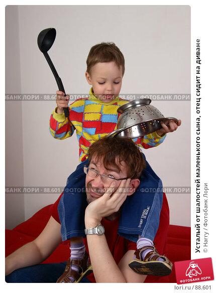 Усталый от шалостей маленького сына, отец сидит на диване, фото № 88601, снято 4 июня 2007 г. (c) Harry / Фотобанк Лори