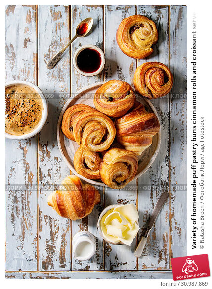 Купить «Variety of homemade puff pastry buns cinnamon rolls and croissant served with coffee cup, jam, butter as breakfast over white plank wooden background. Flat lay, space», фото № 30987869, снято 23 июля 2019 г. (c) age Fotostock / Фотобанк Лори