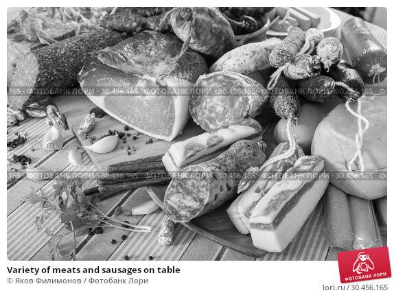 Variety of meats and sausages on table. Стоковое фото, фотограф Яков Филимонов / Фотобанк Лори