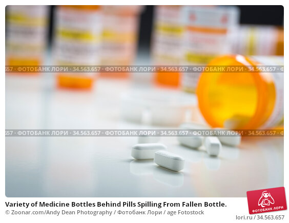 Variety of Medicine Bottles Behind Pills Spilling From Fallen Bottle. Стоковое фото, фотограф Zoonar.com/Andy Dean Photography / age Fotostock / Фотобанк Лори