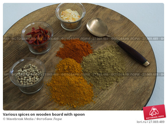 Various spices on wooden board with spoon, фото № 27069489, снято 5 июня 2017 г. (c) Wavebreak Media / Фотобанк Лори
