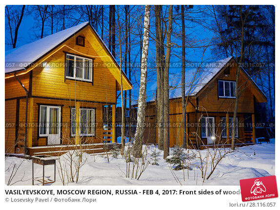 Купить «VASILYEVSKOYE, MOSCOW REGION, RUSSIA - FEB 4, 2017: Front sides of wooden cottages in forest on early winter morning at Provence-Hotel Four Seasons», фото № 28116057, снято 4 февраля 2017 г. (c) Losevsky Pavel / Фотобанк Лори