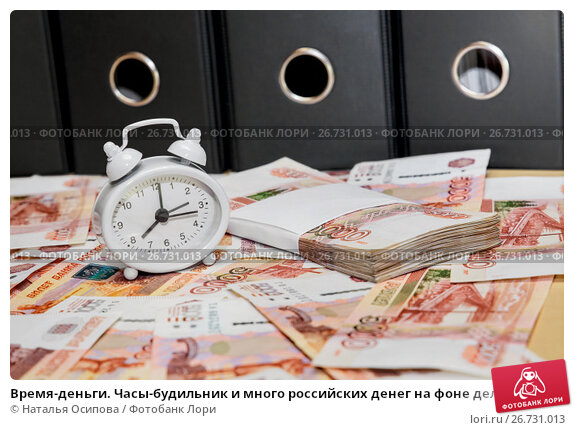 Купить «Время-деньги. Часы-будильник и много российских денег на фоне деловых папок», фото № 26731013, снято 3 августа 2017 г. (c) Наталья Осипова / Фотобанк Лори