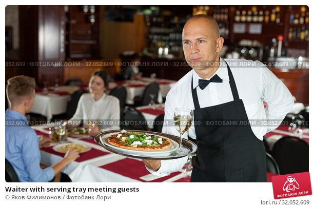 Waiter with serving tray meeting guests. Стоковое фото, фотограф Яков Филимонов / Фотобанк Лори