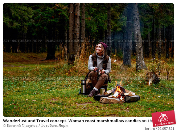 Купить «Wanderlust and Travel concept. Woman roast marshmallow candies on the campfire in forest. Spring or autumn camping», фото № 29057521, снято 6 октября 2016 г. (c) Евгений Глазунов / Фотобанк Лори