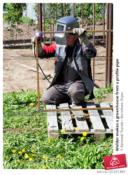 Купить «Welder makes a greenhouse from a profile pipe», фото № 27211857, снято 24 мая 2014 г. (c) Евгений Ткачёв / Фотобанк Лори