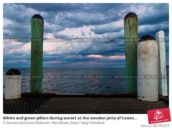 White and green pillars during sunset at the wooden jetty of Cowes... Стоковое фото, фотограф Zoonar.com/Loes KIeboom / easy Fotostock / Фотобанк Лори