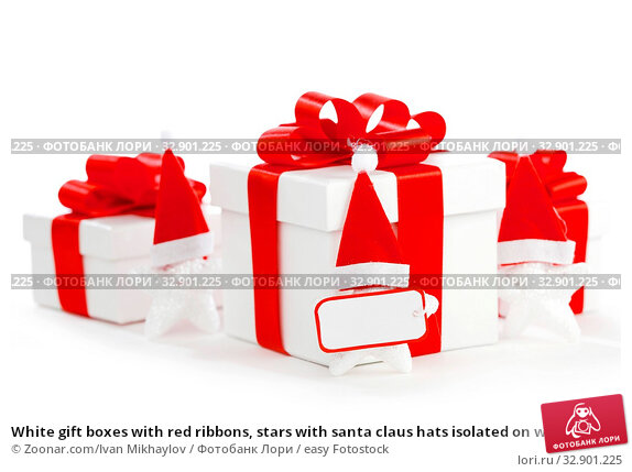 White gift boxes with red ribbons, stars with santa claus hats isolated on white background. Стоковое фото, фотограф Zoonar.com/Ivan Mikhaylov / easy Fotostock / Фотобанк Лори