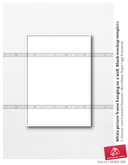 White picture frame hanging on a wall. Blank mockup template. Стоковое фото, фотограф Zoonar.com/Laurent Davoust / age Fotostock / Фотобанк Лори