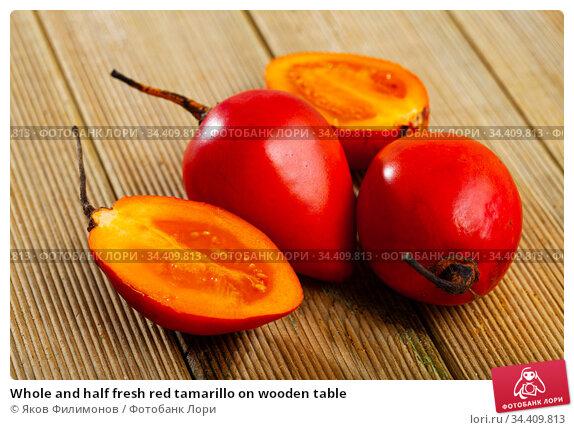 Whole and half fresh red tamarillo on wooden table. Стоковое фото, фотограф Яков Филимонов / Фотобанк Лори