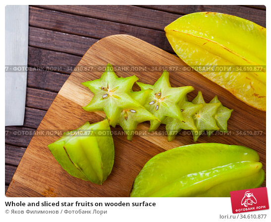 Whole and sliced star fruits on wooden surface. Стоковое фото, фотограф Яков Филимонов / Фотобанк Лори