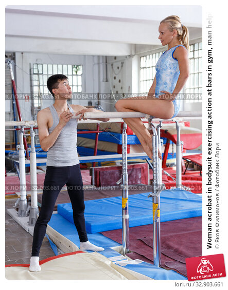 Woman acrobat in bodysuit exercising action at bars in gym, man helping. Стоковое фото, фотограф Яков Филимонов / Фотобанк Лори