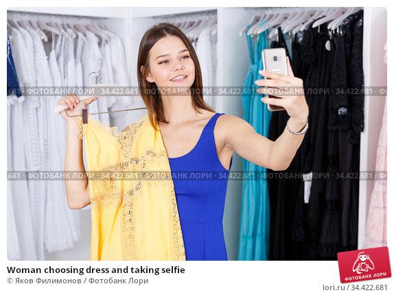 Woman choosing dress and taking selfie. Стоковое фото, фотограф Яков Филимонов / Фотобанк Лори