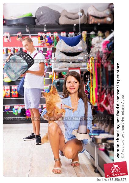 woman choosing pet food dispenser in pet store. Стоковое фото, фотограф Яков Филимонов / Фотобанк Лори
