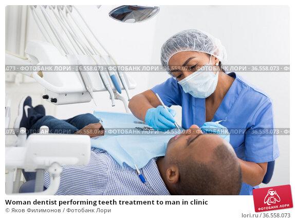 Woman dentist performing teeth treatment to man in clinic. Стоковое фото, фотограф Яков Филимонов / Фотобанк Лори
